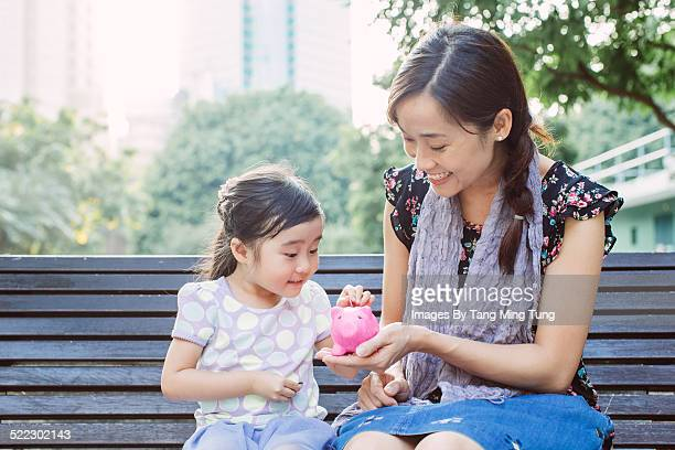 Toddler inserting coins in piggy bank with mom i