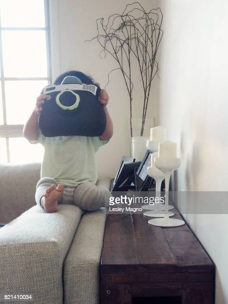 toddler is posing with a camera cushion and sitting on sofa