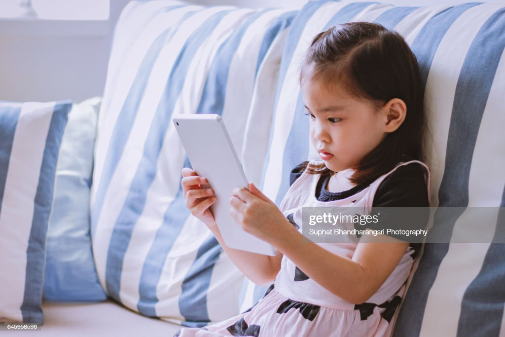 Toddler is reading cartoon on a tablet : Stock Photo