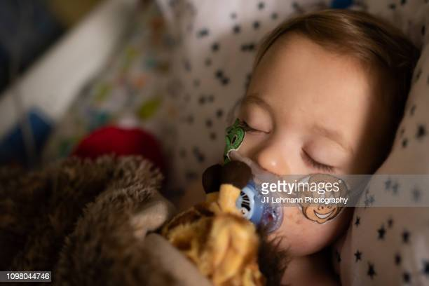 toddler is sick in picu with rsv and has iv and oxygen - breathing device stock pictures, royalty-free photos & images