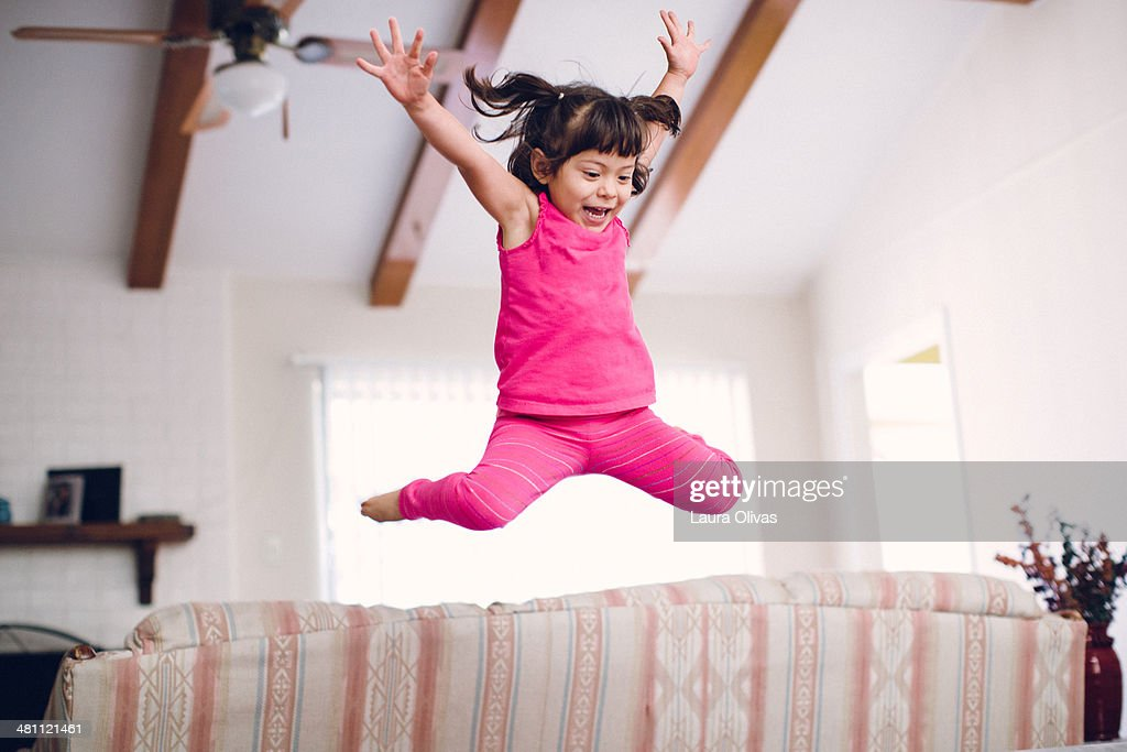 Toddler Jumps High Off The Sofa : Stock Photo
