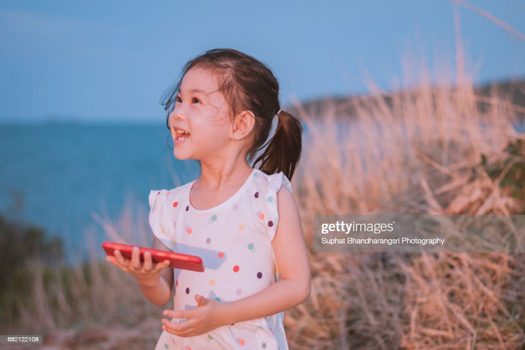 Toddler laughing at the photos she sees on a smartphone : Stock Photo