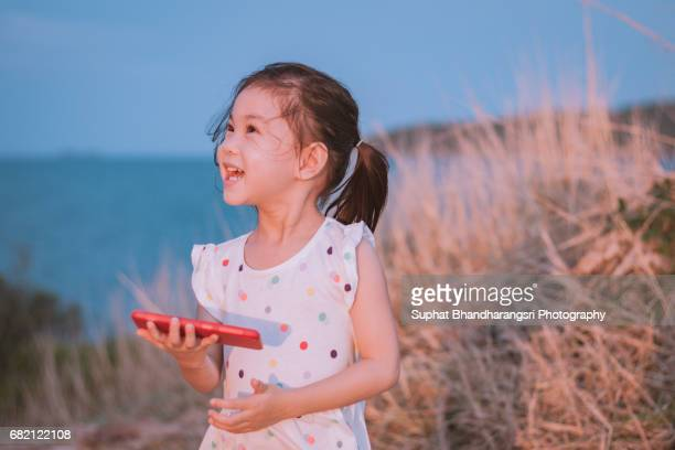 Toddler laughing at the photos she sees on a smartphone