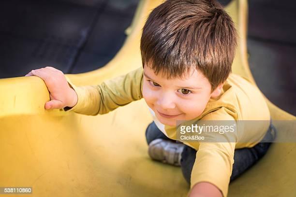 Toddler laughing on playground sliding board