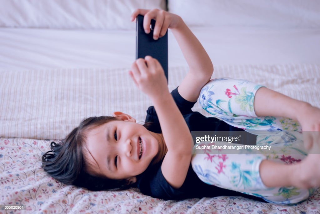 Toddler laughing while watching cartoon on smartphone : Stock Photo