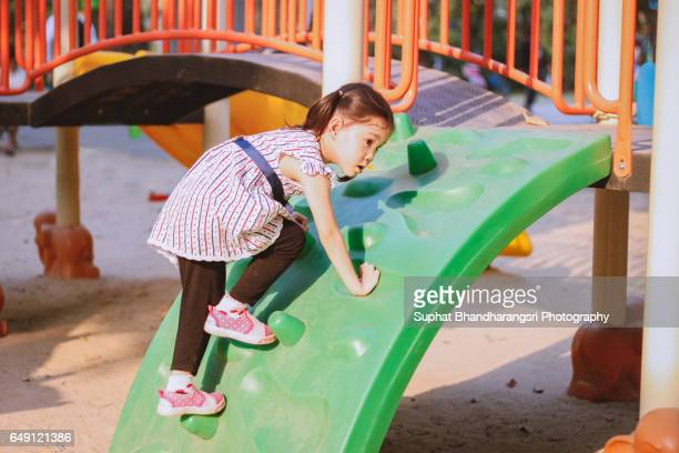 Toddler learning to climb the playhouse