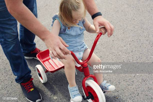 toddler learning to ride a tricycle outdoors - sally anscombe stock pictures, royalty-free photos & images