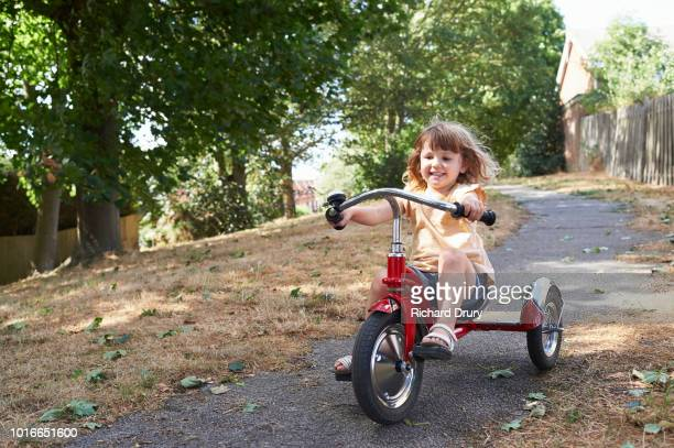 toddler learning to ride her tricycle - tricycle stock pictures, royalty-free photos & images