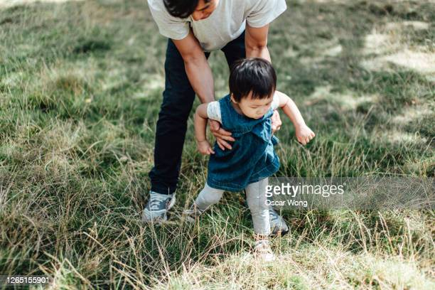 toddler learning to walk with father at the park - life events stock pictures, royalty-free photos & images