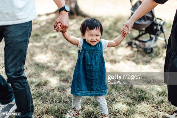 toddler learning to walk with parents at the park - babyhood stock pictures, royalty-free photos & images