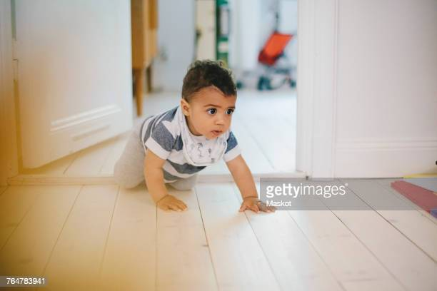 Toddler looking away while crawling on floor at home