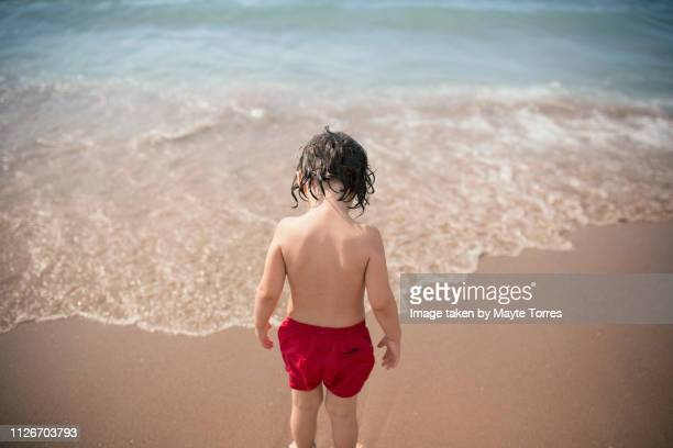 toddler looking down about to enter to the water at the beach - autism awareness stock pictures, royalty-free photos & images