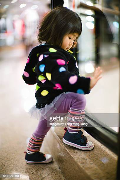 Toddler looking down through glass railing in mall