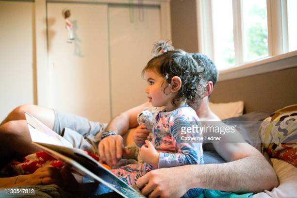 toddler looking happy while dad reads her a book in bed