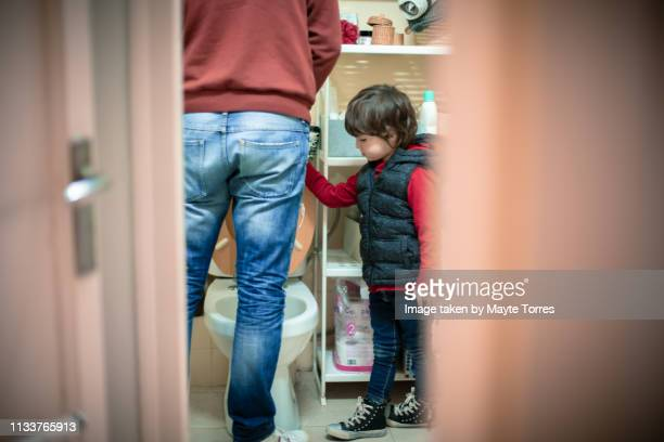 toddler looking how dad is peeing - kids peeing stock pictures, royalty-free photos & images