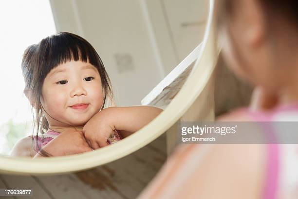 Toddler looking in mirror whilst fastening her dress