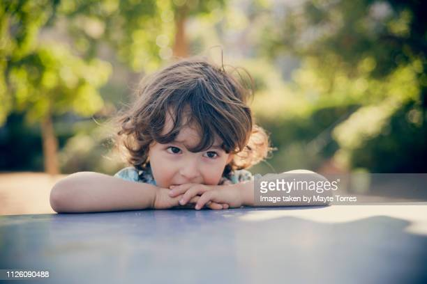 toddler looking sad resting on a table at the park - autism awareness stock pictures, royalty-free photos & images