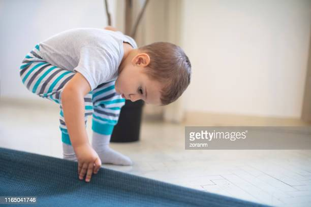 toddler looking under the carpet - bent over babes stock pictures, royalty-free photos & images
