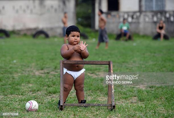 A toddler looks at garifuna boys playing football in a beach of El Triunfo de la Cruz community in the Hondurean Caribbean on June 10 2014 AFP...