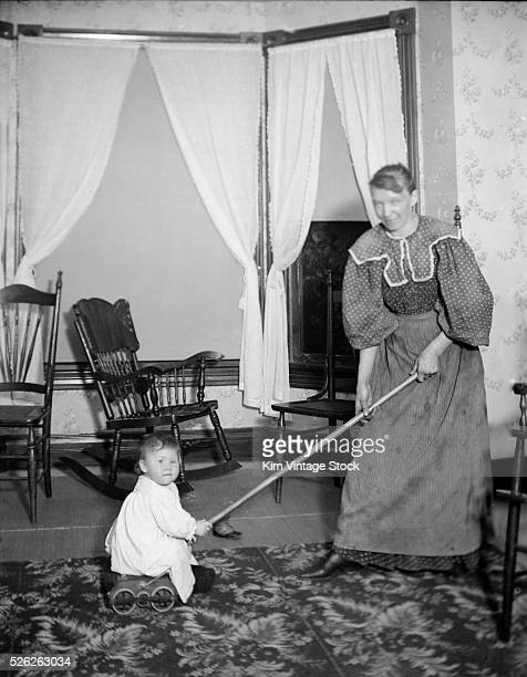 A toddler looks determined to keep his mother from using a modern carpet sweeper on their turnofthe20th century home