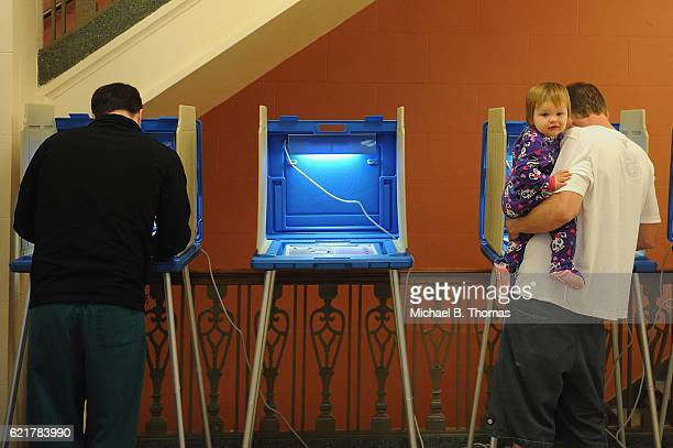 A toddler looks on as people vote in the 2016 Presidential elections at the Alton City Hall on November 8 2016 in Alton Illinois Americans today will...