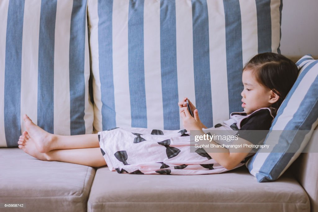 Toddler lying down watching her favourite video : Stock Photo