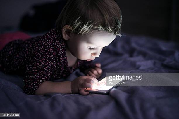 Toddler lying on bed playing with smartphone