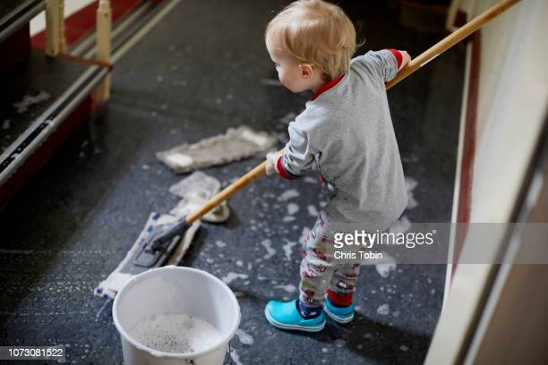 toddler mopping the stairwell - 児童就労 ストックフォトと画像