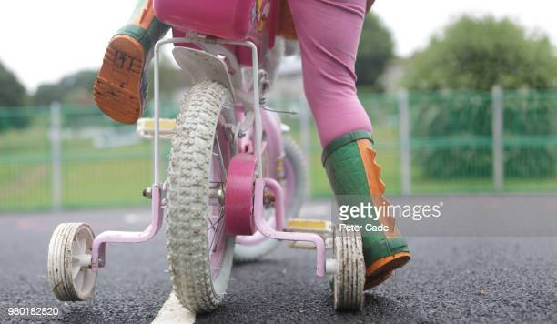 toddler on bicycle with stabilizers - protection stock pictures, royalty-free photos & images