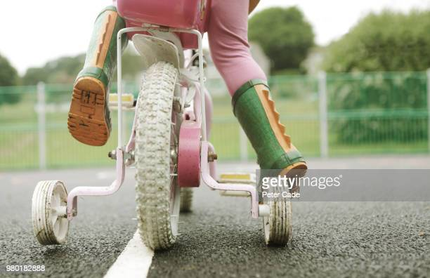 toddler on bicycle with stabilizers - prop stock pictures, royalty-free photos & images