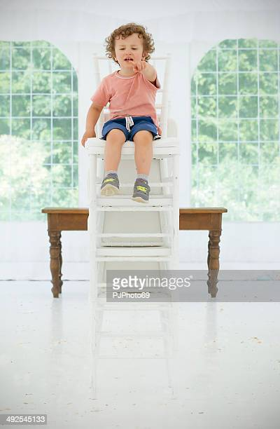 Toddler on tower of white chairs