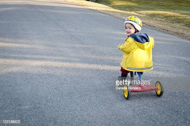 toddler on tricycle - gabardina ropa impermeable fotografías e imágenes de stock