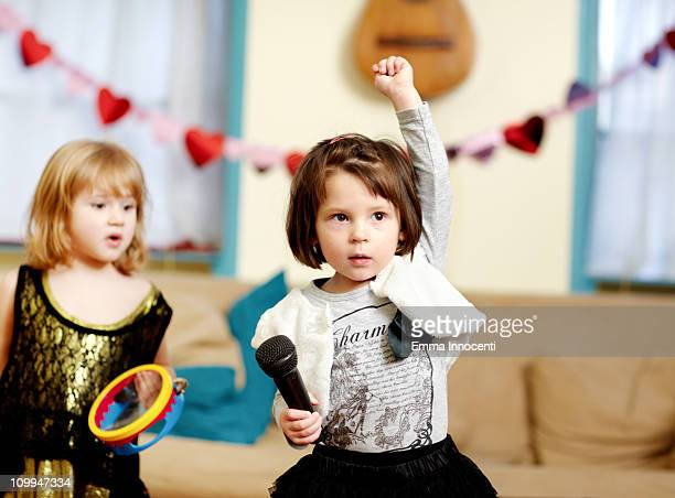 Toddler, one arm raised, microphone, serious