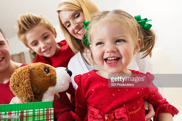 Toddler opening presents with family on Christmas day