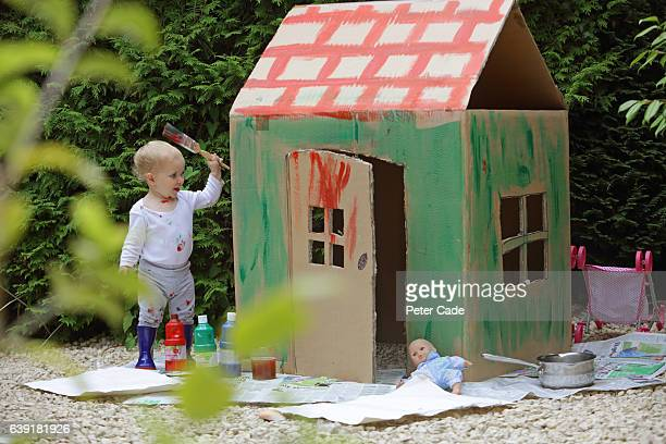 Toddler painting cardboard house in garden
