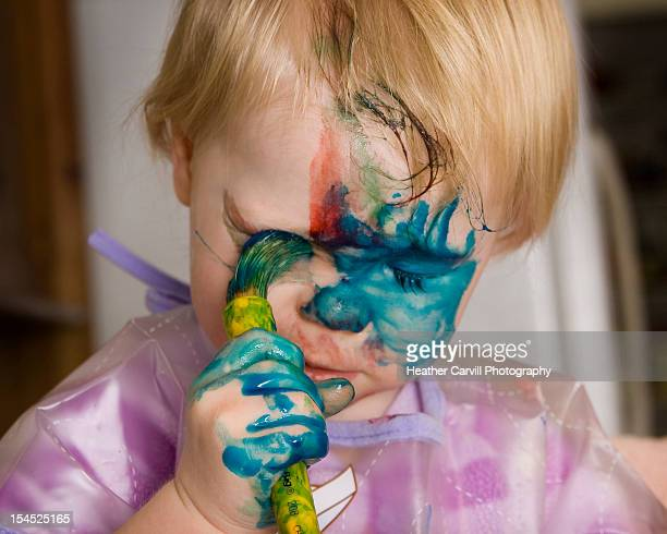 Toddler painting her face blue with fingerpaints