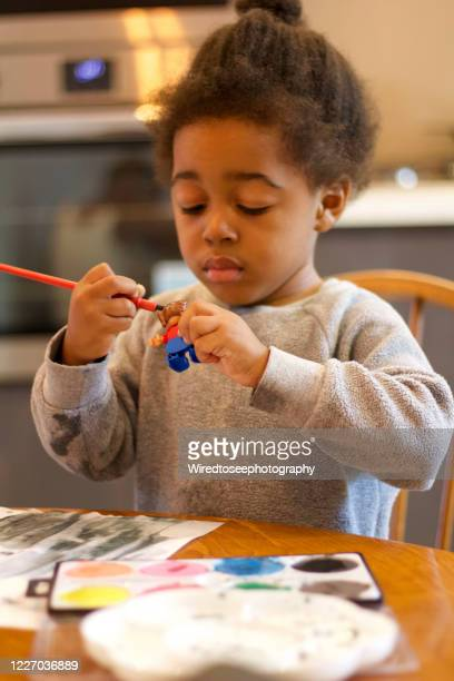 toddler painting his toy at the kitchen table - social justice concept stock pictures, royalty-free photos & images