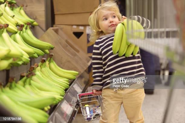 toddler picking bananas in supermarket - supermarket stock pictures, royalty-free photos & images