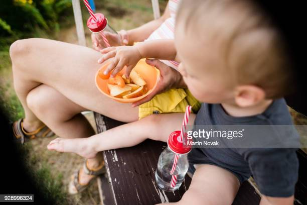 Toddler picking up apple slice from a bowl