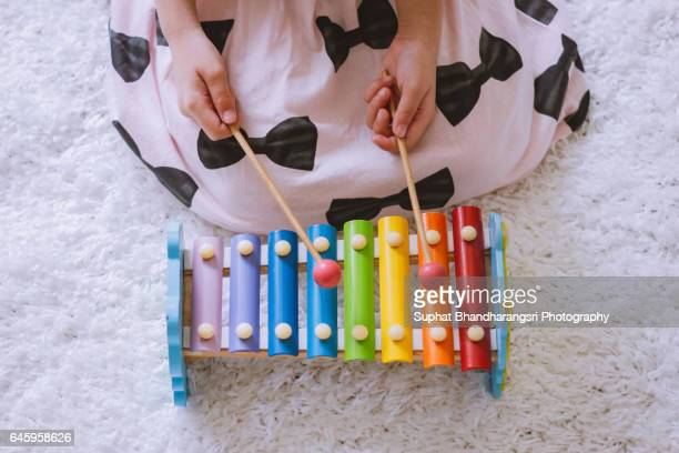 Toddler playing a xylophone at home