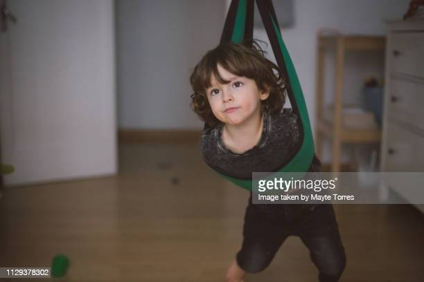 Toddler playing in the swing at home