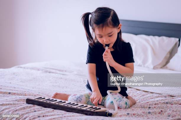 Toddler playing melodian at home