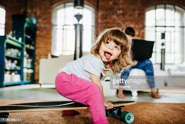 toddler playing on skateboard indoors - peuter stockfoto's en -beelden