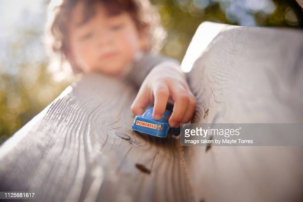 toddler playing with a blue car at the playground - autism awareness stock pictures, royalty-free photos & images