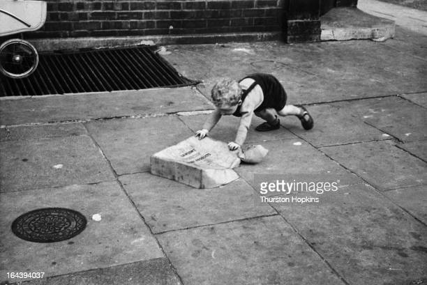 A toddler playing with an old box in a London street August 1954 Original publication Picture Post 7230 Children Of The Streets pub 7th August 1954