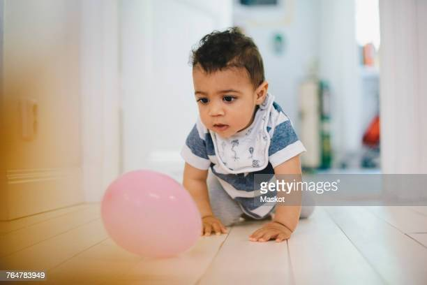 Toddler playing with balloon while crawling on floor at home