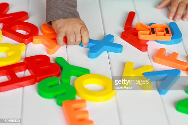 Toddler playing with colorful letters