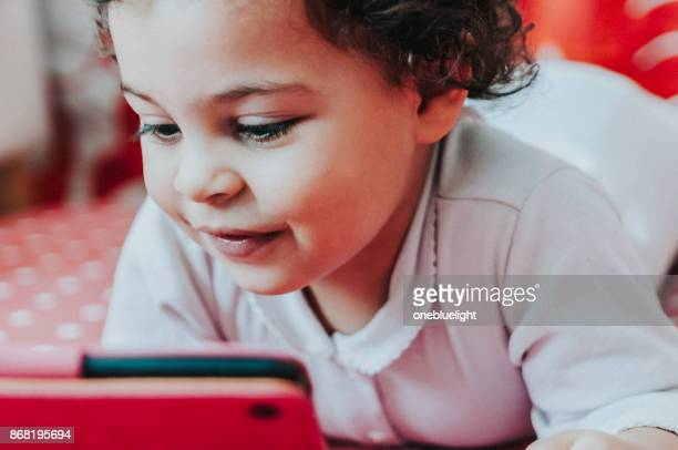 toddler playing with digital tablet. - onebluelight stock pictures, royalty-free photos & images