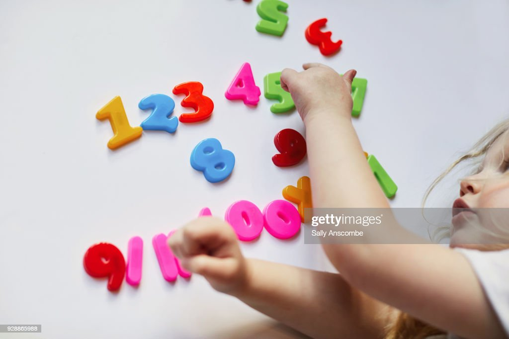Toddler playing with magnetic letters and numbers : Stock Photo