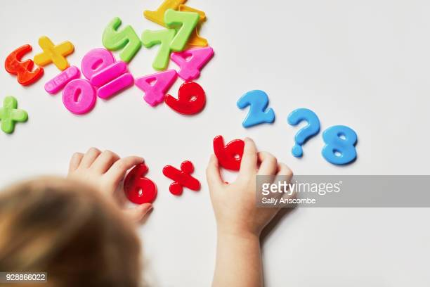 Toddler playing with magnetic letters and numbers